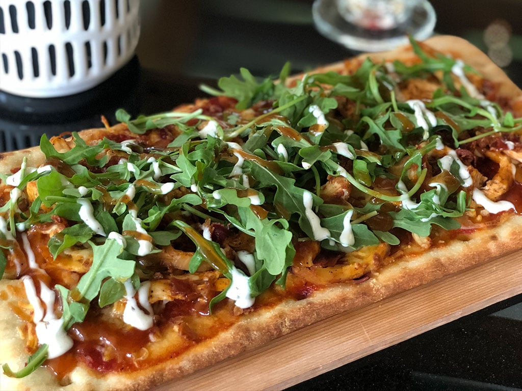 image of flatbread pizza topped with arugula